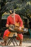 Manlig gatakonstnär i den Budapest Ungern som bär en röd traditionell dräkt som spelar ett gammalt träinstrument Fotografering för Bildbyråer