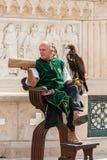 Manlig gatakonstnär på en plaza i den Budapest Ungern som bär en grön traditionell dräkt som rymmer en fågel av rovet Arkivbild