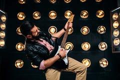 Manlig gitarrist på etapp med garneringar av ljus arkivbilder