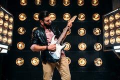 Manlig gitarrist på etapp med garneringar av ljus royaltyfri foto