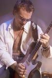 Manlig gitarrist Playing den elektriska gitarren Skjutit med Strobes fotografering för bildbyråer