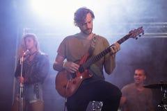 Manlig gitarrist som perfoming med gitarren under musikfestival royaltyfri bild