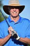 Manlig golfare för konditionpensionär som ler med Golf Club som spelar golf arkivbilder