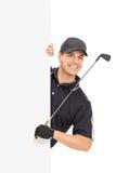 Manlig golfare som poserar bak en tom panel Arkivfoton