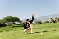 Manlig golfare som ställer upp putt Arkivbild