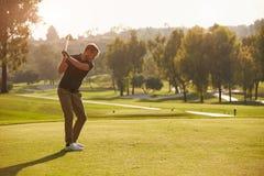 Manlig golfare som ställer upp utslagsplatsen som skjutas på golfbana Fotografering för Bildbyråer