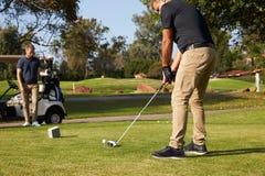 Manlig golfare som ställer upp utslagsplatsen som skjutas på golfbana Arkivfoto