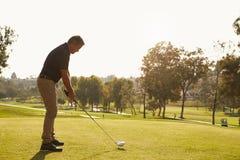 Manlig golfare som ställer upp utslagsplatsen som skjutas på golfbana Arkivfoton