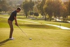 Manlig golfare som ställer upp utslagsplatsen som skjutas på golfbana Royaltyfria Foton