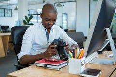 Manlig grafisk formgivare som granskar fångade bilder i hans digitala kamera på skrivbordet Fotografering för Bildbyråer