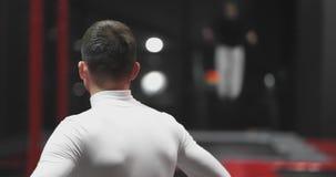 Manlig gymnast i trampolinmitten som håller ögonen på tillbaka kapaciteten av trickrivaler arkivfilmer