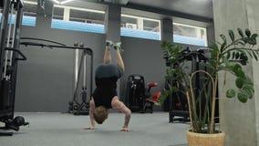 Manlig gymnast som g?r p? h?nder p? idrottshallen Ung stark muskulös man som går på händer stock video