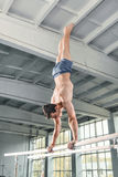 Manlig gymnast som utför handstans på barr Royaltyfri Bild