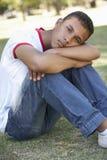 Manlig högskolestudent Sitting In Park som ser olycklig Fotografering för Bildbyråer