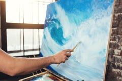 Manlig hand av den hållande målarpenseln för konstnär på bakgrund av kanfas på staffli Yrkesmässig våg för målareteckningshav i v royaltyfri fotografi