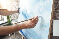 Manlig hand av den hållande målarpenseln för konstnärcloseup på bakgrund av kanfas på staffli Våg för målareteckningshav i vindst arkivbild