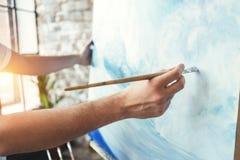 Manlig hand av den hållande målarpenseln för konstnärcloseup på bakgrund av kanfas på staffli Våg för målareteckningshav i vindst arkivfoto
