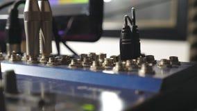 Manlig hand av den solida teknikern som pluggar den ljudsignal kabeln av en blandarepanel Ljudsignal redaktör som arbetar i moder arkivfilmer