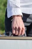 Manlig hand enchained till resväskan royaltyfria foton