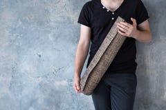 Manlig hand för Closeup som rymmer yoga matt över ljus grå bakgrund, kopieringsutrymme royaltyfri fotografi