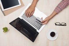 Manlig hand genom att använda bärbara datorn med kreditering som direktanslutet gör betalning på skrivbordet Arkivfoton