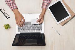 Manlig hand genom att använda bärbara datorn med kreditering som direktanslutet gör betalning på skrivbordet Royaltyfria Bilder