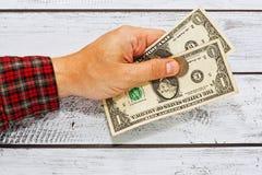 Manlig hand i den rutiga skjortan som rymmer två US dollar Arkivbild