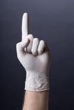 Manlig hand i latexhandsken som pekar upp royaltyfria bilder