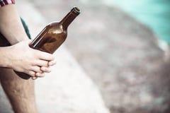 Manlig hand med den utomhus- vinflaskan arkivbilder