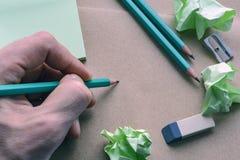 Manlig hand med en blyertspenna, vässare, radergummi, klistermärkear, brunt papper med skrynkliga klibbiga anmärkningar, idérik k Royaltyfria Bilder
