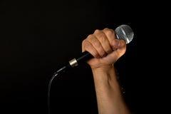Manlig hand med mikrofonen som isoleras på svart Arkivbilder