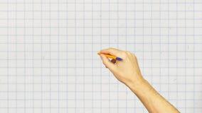 Manlig hand med pennhandstil på det vita rutiga bakgrundsslutet upp arkivfilmer