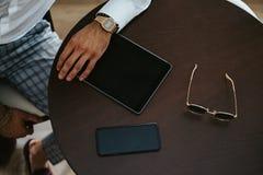 Manlig hand på en tabell med minnestavlan, telefonen och solglasögon arkivfoton