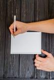 Manlig hand som är skriftlig på ram Arkivbilder