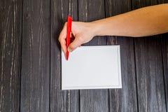 Manlig hand som är skriftlig på ram Arkivbild