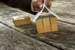 Manlig hand som överst förlägger ett pappers- tak av miniatyrhuset Royaltyfri Bild