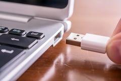 Manlig hand som förbinder en vit USB kabel till USB porten av en liten anteckningsbok Arkivbild
