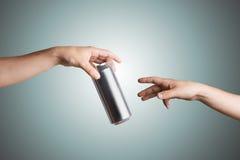 Manlig hand som ger en ölburk till en annan person Arkivfoto