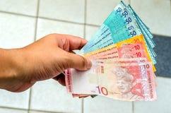 Manlig hand som ger pengar Arkivbilder