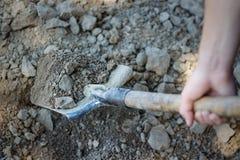 Manlig hand som gräver med en skyffel Jorden i skyffeln Closeu royaltyfri bild