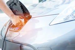 Manlig hand som laddar ett e-bilbatteri arkivbilder