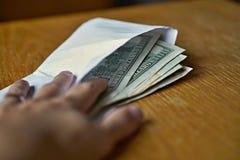 Manlig hand som mycket öppnar ett vitt kuvert av amerikanska dollar (USD, US dollar) på trätabellen som ett symbol av den kontant Royaltyfri Fotografi