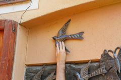 Manlig hand som når för den dekorativa metallfågeln som är till salu på den gamla gatan i Besalu, Spanien Royaltyfri Foto