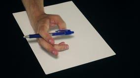 Manlig hand som nervöst spelar med en penna på en svart bakgrund stock video