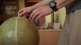 Manlig hand som rotera det gamla jordklotet arkivfilmer