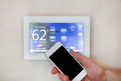 Manlig hand som rymmer den smarta telefonen för att fungera att värma eller att kyla via den digitala pekskärmtermostaten för hem royaltyfria bilder