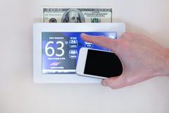 Manlig hand som rymmer den smarta telefonen för att fungera att värma eller att kyla via den digitala pekskärmtermostaten för hem royaltyfri foto