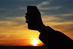 Manlig hand som rymmer den smarta telefonen på solnedgången royaltyfri fotografi