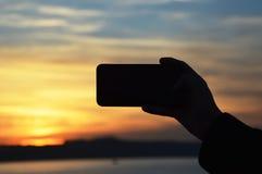 Manlig hand som rymmer den smarta telefonen på solnedgången royaltyfri foto