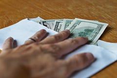 Manlig hand som rymmer dess fingrar på det vita kuvertet fulla av amerikanska dollar (USD, US dollar) på trätabellen som ett symb Royaltyfri Foto